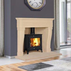Large white stone fireplace with black log burner fire, Feature clock above fireplace, grey rug on floor, Sandridge Stone Fireplaces, Limestone, Bath Stone, Portland Limestone, Melksham, Wiltshire