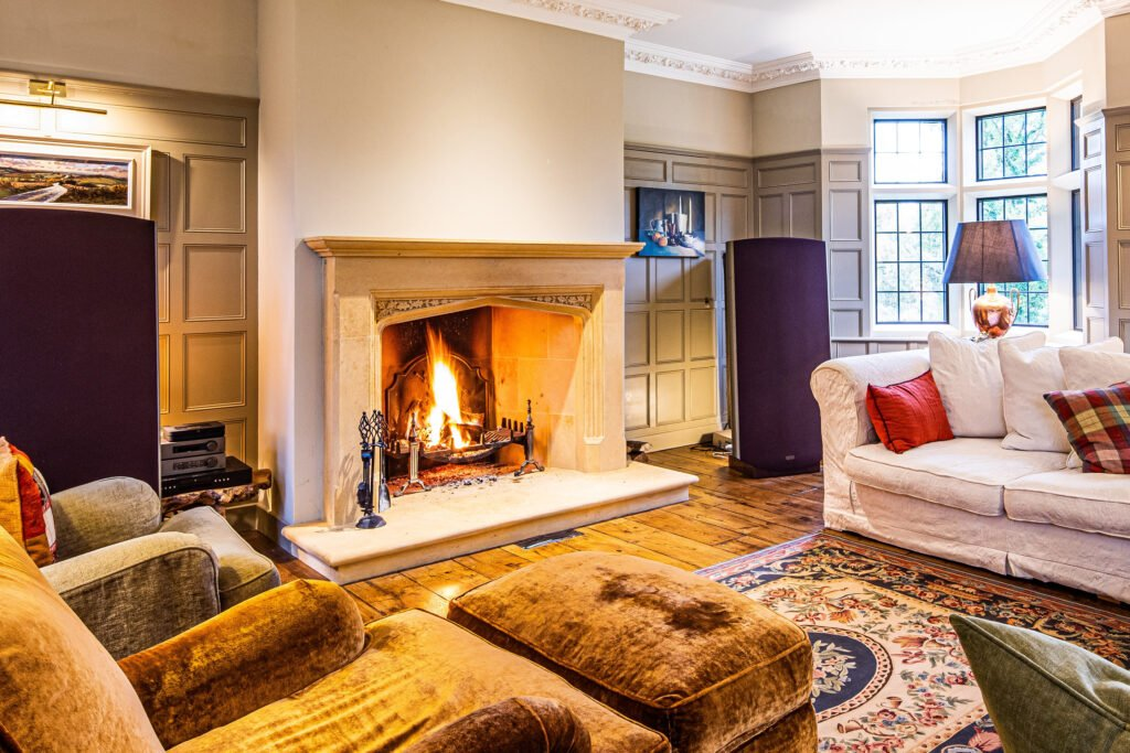 Luxury country living space, with sofas, wood panelled walls, bath stone fireplace with roaring fire, Sandridge Stone Fireplaces, Limestone, Bath Stone, Portland Limestone, Melksham, Wiltshire