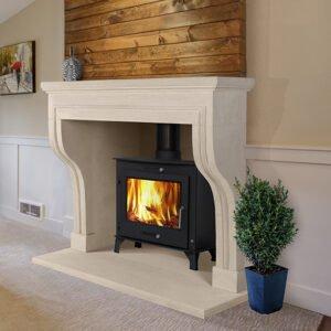 Honnecourt fireplace with logburner fire in living space with small shrub and art on wall,Sandridge Stone Fireplaces, Limestone, Bath Stone, Portland Limestone, Melksham, Wiltshire